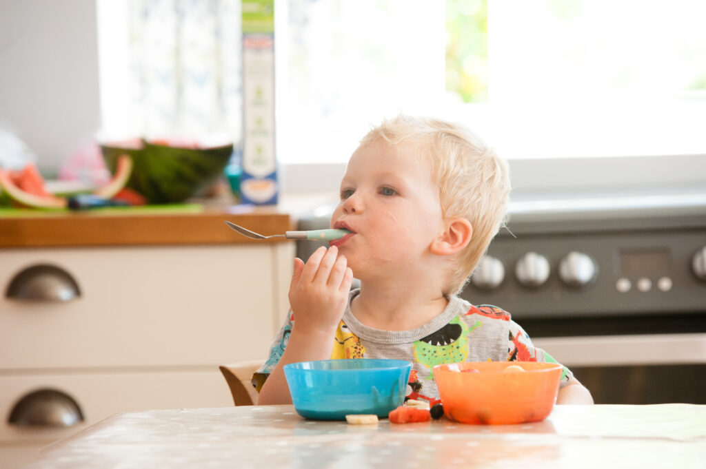 Baby with blue spoon eating from a bowl